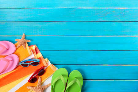 towel beach: Beach scene with orange striped towel, starfish, sunglasses and flip flops on old blue wood decking.  Space for copy. Stock Photo