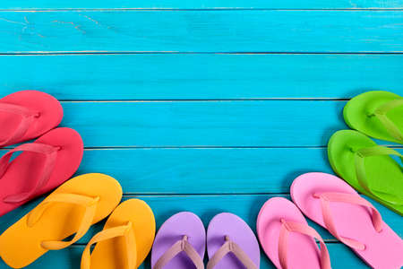decking: Semi circle of colorful flip flops on old weathered blue painted beach decking.  Space for copy.