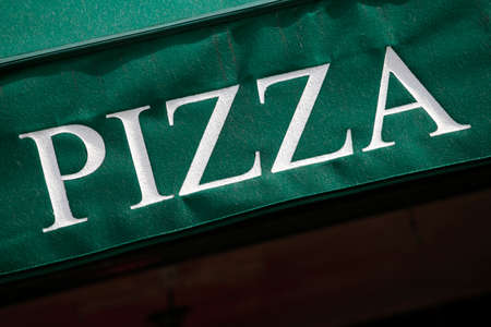 building exteriors: Pizza sign printed on a green entrance canopy.