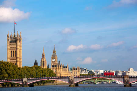 wind down: Landscape view of the UK Houses of Parliament looking down the River Thames towards Westminster.  Blue summer sky and Union Jack flag flying in the wind.  Red double decker bus on Lambeth Bridge.  Space for copy.