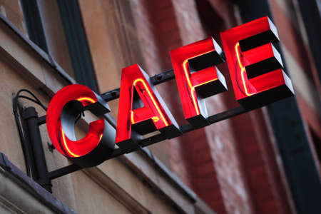 Neon cafe sign with out of focus building in the background.