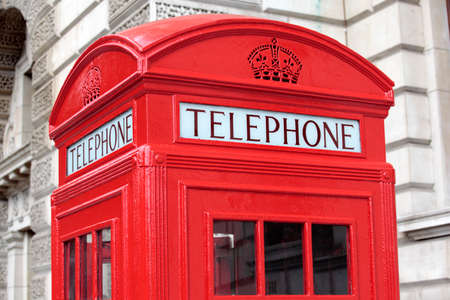 building exteriors: Traditional red telephone box in front of a typical Georgian style London building.