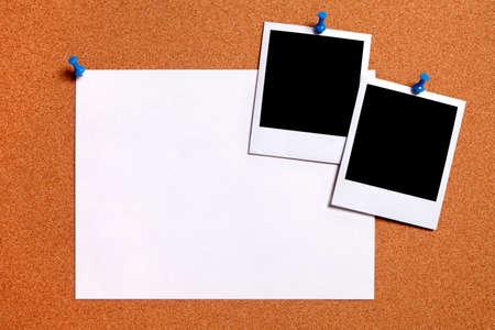 Lege polaroid fotoprints en normaal papier poster vastgemaakt aan een kurk prikbord. Ruimte voor exemplaar.