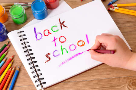 Child writing the words Back to School on a white folded notebook with various paints, crayons and pencils on a school desk.