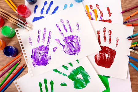 handprints: Painted handprints with art and craft equipment on a school table. Stock Photo