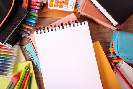 utiles escolares: Escritorio del Estudiante ocupado con almohadilla abierta boceto, bolso de escuela, los libros de texto y varios lápices y lápices de colores.