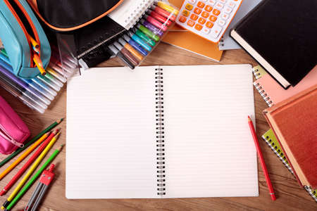 Busy student's desk with open notebook, school bag, text books and various pencils and crayons.