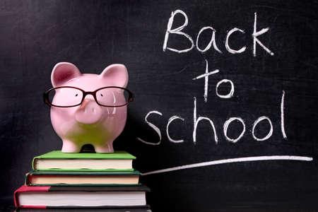 Tirelire rose avec des lunettes debout sur les manuels devant un tableau noir avec le dos à un message de l'école.