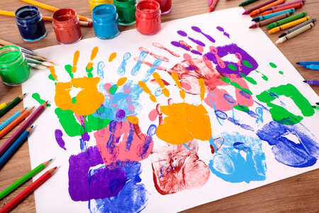 Painted handprints with art and craft equipment on a school table.  Shallow depth of field with sharp focus on the nearest handprints and blurred distant background.