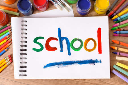 art and craft equipment: The word School painted on a white art book with various paints, crayons and pencils on a school desk.
