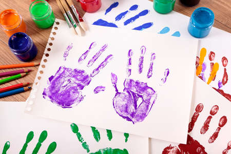 art and craft equipment: Painted handprints with art and craft equipment on a school table. Stock Photo