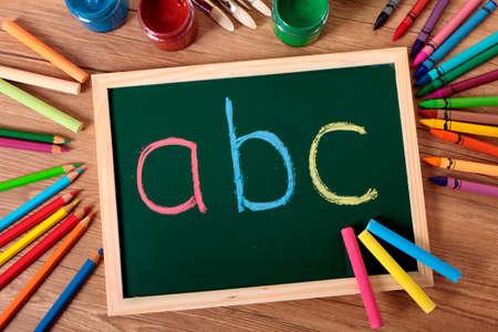 ABC geschreven in kleur krijt op een kleine elementaire schoolbord met verschillende verf, kleurpotloden en potloden op een school bureau.