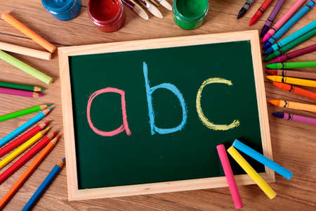 abc: ABC written in color chalk on a small elementary blackboard with various paints, crayons and pencils on a school desk.