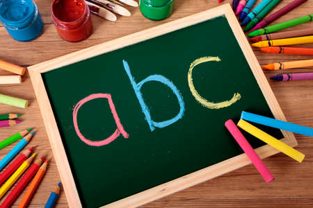 teaching crayons: ABC written in color chalk on a small elementary blackboard with various paints, crayons and pencils on a school desk.