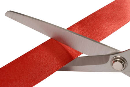 snipping: Close-up of scissors cutting red ribbon or tape against a white background Stock Photo