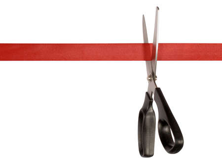 Scissors cutting red ribbon or tape against a white background Stock Photo