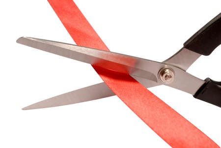 bureaucratic: Close-up of scissors cutting red ribbon or tape against a white background Stock Photo