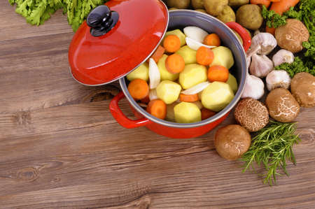 stockpot: Red casserole pot with organic vegetables and herbs on a wooden table with copy space.