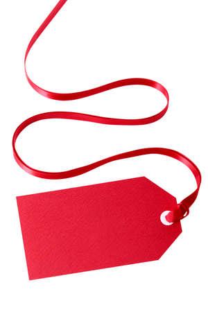 Red geschenk tag of prijs kaartje met een rood lint geïsoleerd op wit (met pad). Scherpe focus op de tag met lint geleidelijk vervaagd.