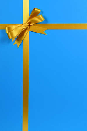 a bow: Gold gift ribbon on blue background.