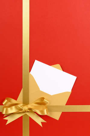 wrapped gift: Red and gold gift with blank invitation or greetings card. Stock Photo