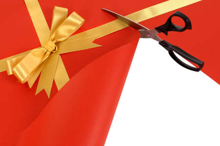 unwrapping: Scissors cutting open red and gold Christmas gift