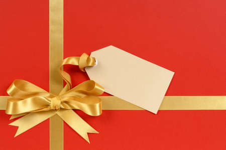 blank tag: Red and gold gift with blank tag or label. Stock Photo