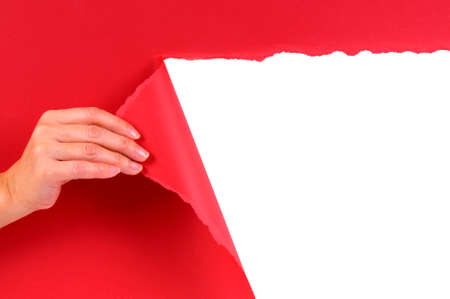 tearing: Hand tearing red paper revealing white background. Stock Photo