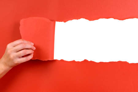 uncovering: Hand tearing red paper background Stock Photo