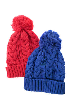 bobble: Red and blue cable knit bobble hats or ski hats isolated on a white background. Stock Photo