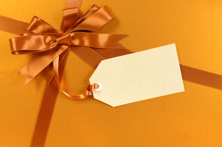 Gold christmas gift background ribbon and bow, gift tag