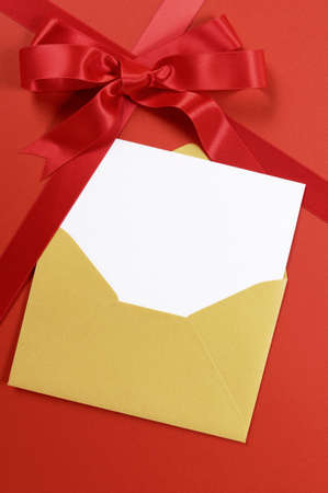 christmas bow: Red gift background with gold envelope and blank invitation or greetings card. Stock Photo