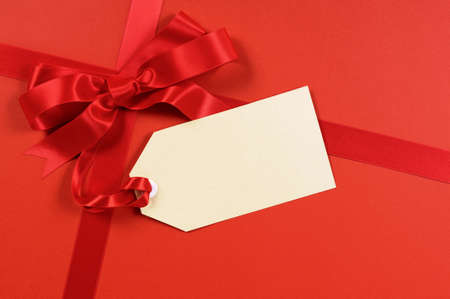 gift tag: Red gift ribbon and bow with blank tag or label