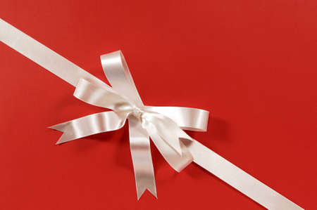 diagonal: Diagonal gift ribbon and bow in white satin on red paper background Stock Photo