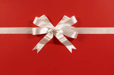white ribbon: White gift ribbon and bow on red paper background horizontal