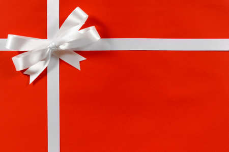 white ribbon: Christmas border frame gift ribbon in white satin on red paper background horizontal Stock Photo