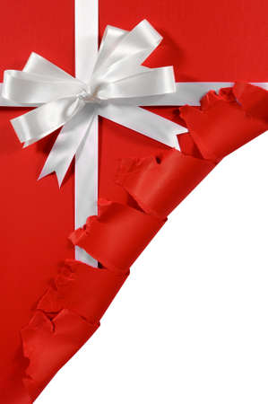 cut or torn paper: Christmas or birthday white satin gift ribbon and bow on red paper background with torn open corner vertical