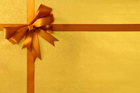 クリスマスや誕生日ギフト背景ゴールド金属箔深い蜂蜜ゴールド リボンと弓 写真素材