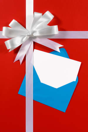 gift ribbon: Christmas or birthday card with gift ribbon and bow in white satin on red paper background with blue envelope and blank message card vertical