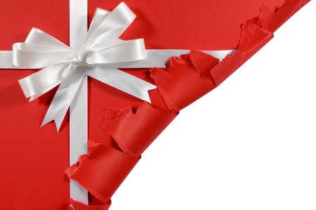 クリスマスや誕生日の白いサテン ギフト リボンと引き裂かれた開いているコーナーと赤い紙の背景にボー 写真素材