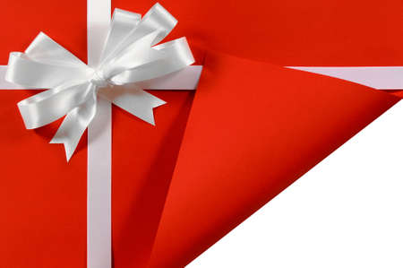 white ribbon: Christmas or birthday white satin gift ribbon and bow on red paper background with open folded corner