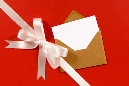 envelopes: White gift ribbon and bow diagonal on red paper background with brown envelope and blank card