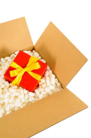 boite carton: Boîte en carton de livraison d'expédition avec un cadeau rouge à l'intérieur et des morceaux d'emballage en polystyrène.