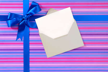 envelope decoration: Blue gift ribbon bow on candy stripe wrapping paper, blank Christmas or birthday card and envelope, copy space