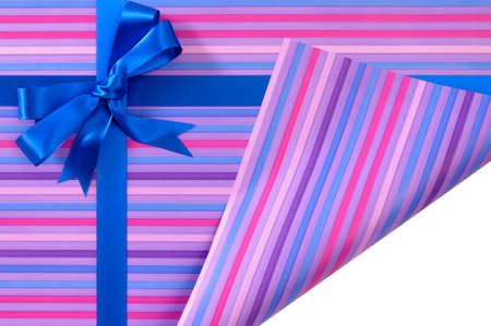 uncovering: Blue gift ribbon bow on candy stripe wrapping paper, corner folded open showing white copy space