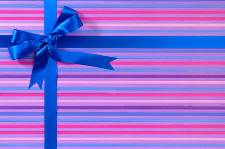blue border: Blue Christmas or birthday gift ribbon bow on candy stripe wrapping paper background Stock Photo