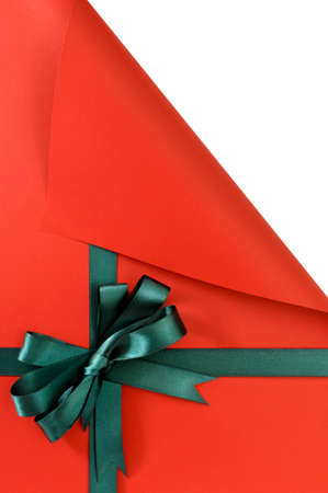 uncovering: Green gift ribbon bow on plain red background paper, top corner curled open showing white copy space, vertical Stock Photo