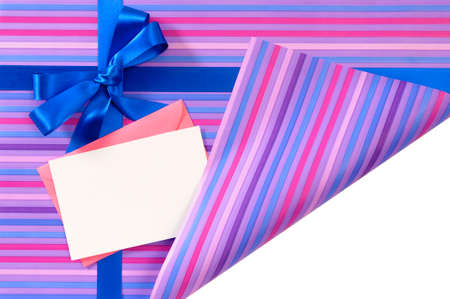 unwrapping: Blue gift ribbon bow on candy stripe wrapping paper, corner folded open revealing white copy space, card and envelope