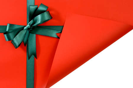 revealing: Green gift ribbon bow on plain red background paper, corner folded open revealing white copy space