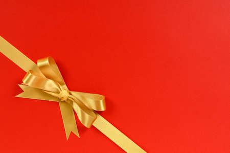 red paper: Gold gift bow ribbon corner diagonal isolated on red wrapping paper background